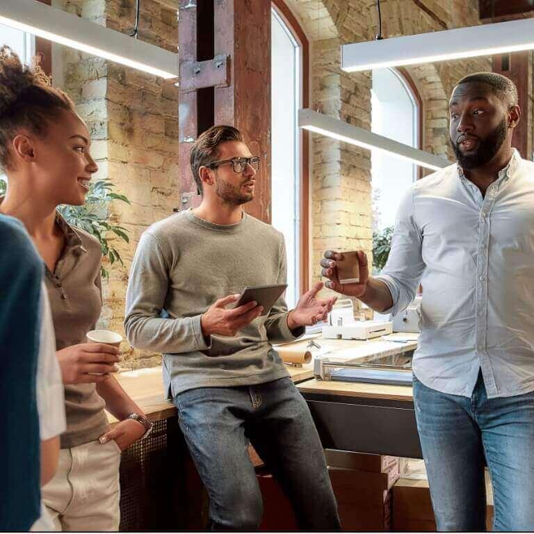 Três pessoas no escritório, tomando café em uma reunião