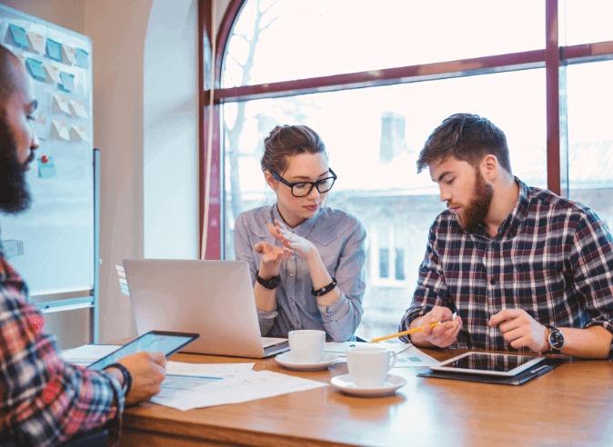 Reunião entre três pessoas debatendo sobre as melhores tecnologias